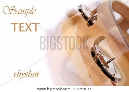 Abstract macro image of tambourine being shaken on white background with copy space.  Intentional motion blur captured with movement during exposure to create effect.