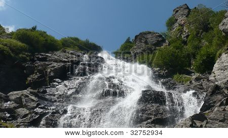 Wonderful landscape Small mountain waterfall rushing over the rocks
