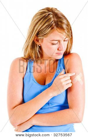 Woman putting a band-aid on her arm isolated over white