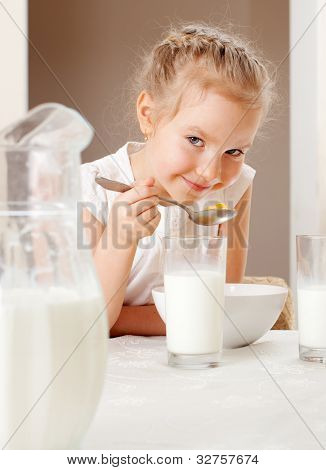 Child eat breakfast. Girl eating cereals with milk