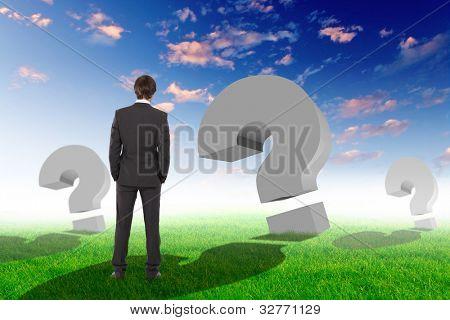 Kaufmann stehen außerhalb mit Fragezeichen um ihn herum
