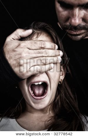 Girl being abused  by an adult man who has a hand covering her eyes while she screams