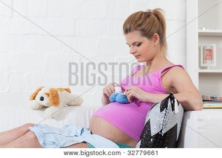 Schwangere Frau mit Kinderkleidung.