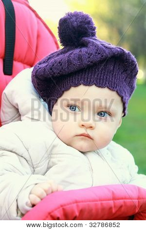 Funny Baby Girl In Hat Outdoor Sit In Stroller And Looking. Closeup Portrait