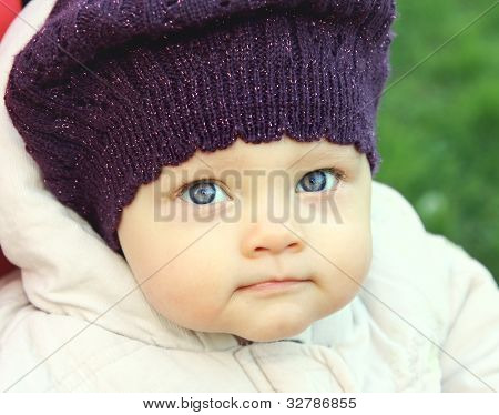 Beautiful Funny Baby In Hat With Big Blue Eyes On Nature Green Background