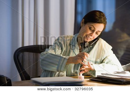Hispanic businesswoman painting fingernails at desk