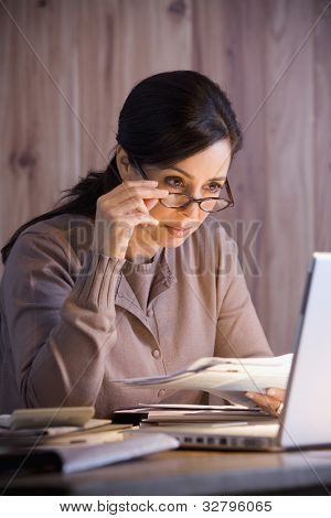 Hispanic businesswoman looking at laptop