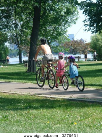 Father Riding Bike In Park With Children