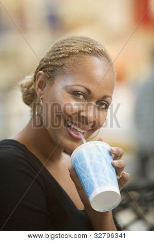 Mixed Race woman drinking fountain soda