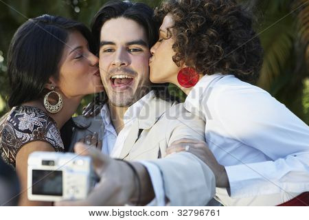 Man taking photograph of two women kissing him