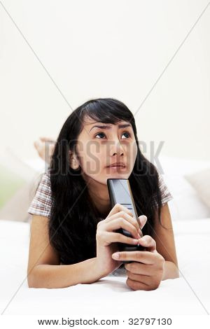 Thoughtful Woman With A Remote Control On Bed
