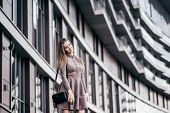 A Young Girl Walks Near The Office With A Handbag On Her Shoulder poster