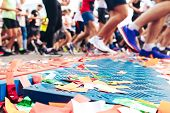 Marathon Start Line With Confetti Strewn On It And Running Athletes In The Distance poster