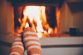 Feet In Wool Striped Socks By The Fireplace. Relaxing At Christmas Fireplace On Winter Holiday Eveni poster
