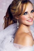 happy beautiful bride with long blond hair in ponytail waring artistic smoky eyeshadow and smiling o