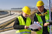 stock photo of vest  - Land surveyors on highway reading geodesist plans use tacheometer - JPG