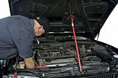 image of auto repair shop  - An auto mechanic works on an engine of an automobile in an auto repair shop