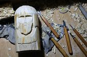 The Process Of Wood Carving. Carved Old Man Or Pagan Deity poster
