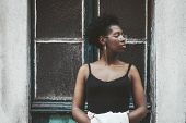 A Charming Young African Female In Spectacles Is Standing In Front Of An Old Antique Wall With A Doo poster