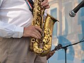 Color photo of a man with a saxophone on stage