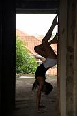 Silhouette Of Asian Beauty Poses Upside Down Yoga Pose In A Building Under Construction. poster