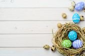 Bright Easter Eggs In Nest And Quail Eggs On The Light Wooden Surface, Close-up. Place To Insert You poster