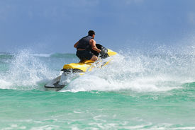 stock photo of waverunner  - Man have fun on Wave Runner turns fast on the water - JPG