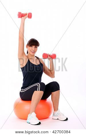 Beautiful woman exercising with fitball and dumbbells isolated over white background