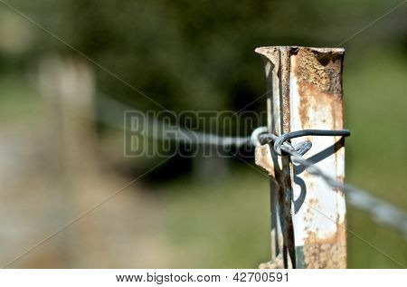 Close up of a barbed wire fence post