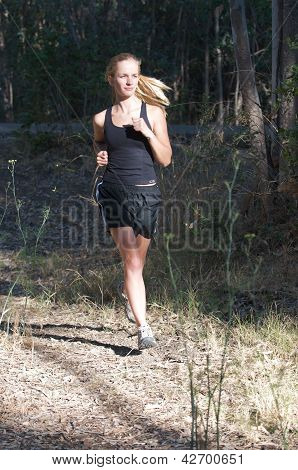 Young woman in black jogs in the forest