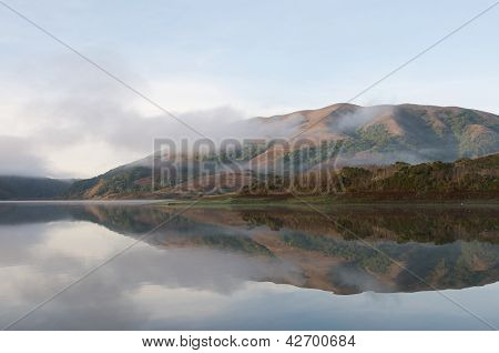 Hills reflected in surface of lake foggy morning