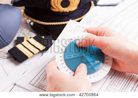 Close up of an airplane pilot hands with holding pattern calculator with equipment including hat, epaulettes and other documents in background
