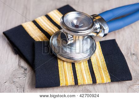 Close up of an airplane pilot's epaluetes with doctor's stethoscope. Conceptual image of medical exam.