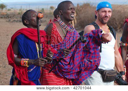 Afrikanische Männer vom Stamm der Masai tanzen mit einem touristischen