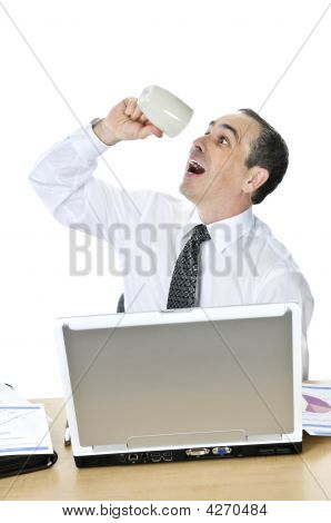 Overworked Businessman At His Desk On White Background