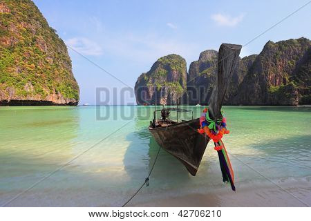 Picturesque green islands of the Thai coast. Emerald sea and thin white sand. On a beach the tourist boat decorated with red silk scarfs and a flower wreath is moored