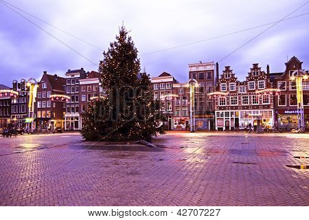 AMSTERDAM, THE NETHERLANDS DECEMBER 25: Christmas in Amsterdam on the famous Nieuwmarkt with enlightened christmas tree and medieval houses at sunset on 25th of december 2012  in the Netherlands