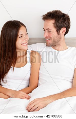 Loving young couple sitting up in the comfort of their bed looking into each others eyes and smiling happily. Interracial couple, Asian woman, Caucasian man.