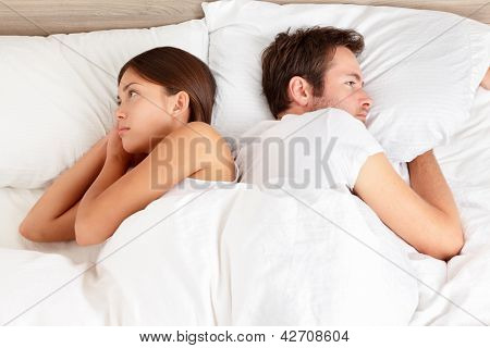 Upset young couple having marital problems or a disagreement lying side by side in bed facing in opposite directions ignoring one another. Interracial couple, Asian woman, Caucasian man.