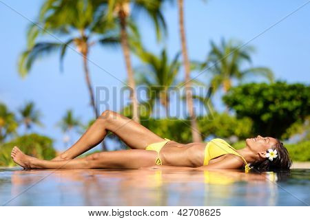 Beautiful vacation woman relaxing at a tropical spa resort lying on edge of infinity pool sunbathing in her bikini against a backdrop of palm trees. Pretty multicultural Asian Caucasian female model.