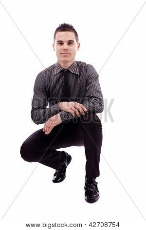 Young Man Sitting In Crouched Position