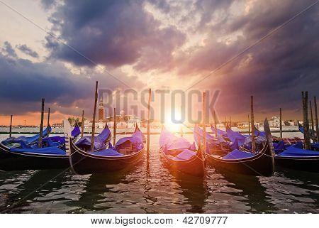 Gondolas Bobbing In Lagoon Outside San Marco Piazza Venice Italy With Sunburst