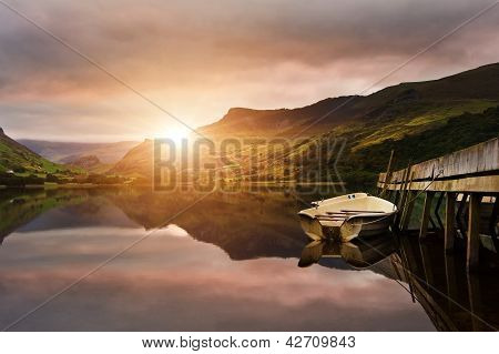 Sunrise Over Lake With Boats Moored At Jetty