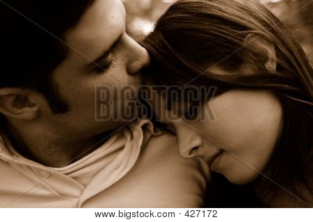 couple in love, man kisses woman's forehead, showing his gentle affection for her. poster. ID: 427172