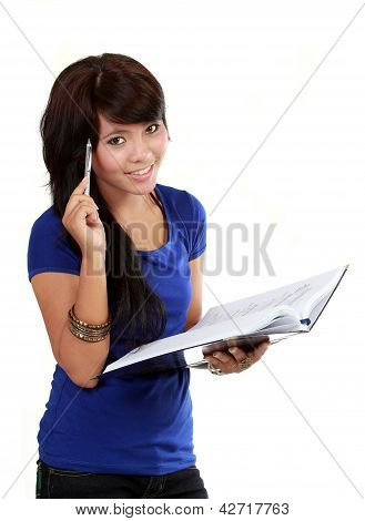 Pretty Young Woman Thinking, Holding Pen And A Notebook