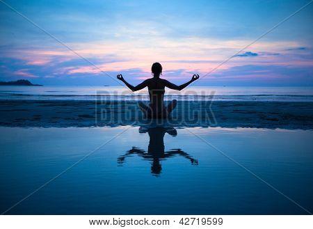 Mujer practicando yoga en la playa al atardecer (con reflejo en el agua)