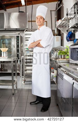 Portrait of young male chef standing with arms crossed in restaurant kitchen