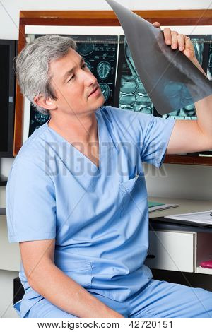 Mature male radiologist analyzing patient's x-ray report at clinic