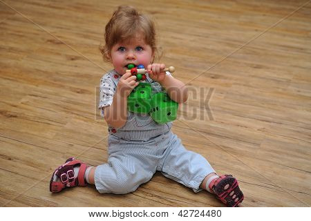 Small Girl Sitting On Wooden Floor And Play With Toys