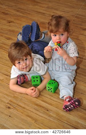 Happy Brother And Sister On Wooden Floor With Toys